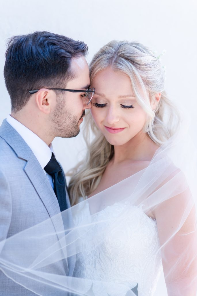 Newlyweds nuzzle under swooped veil